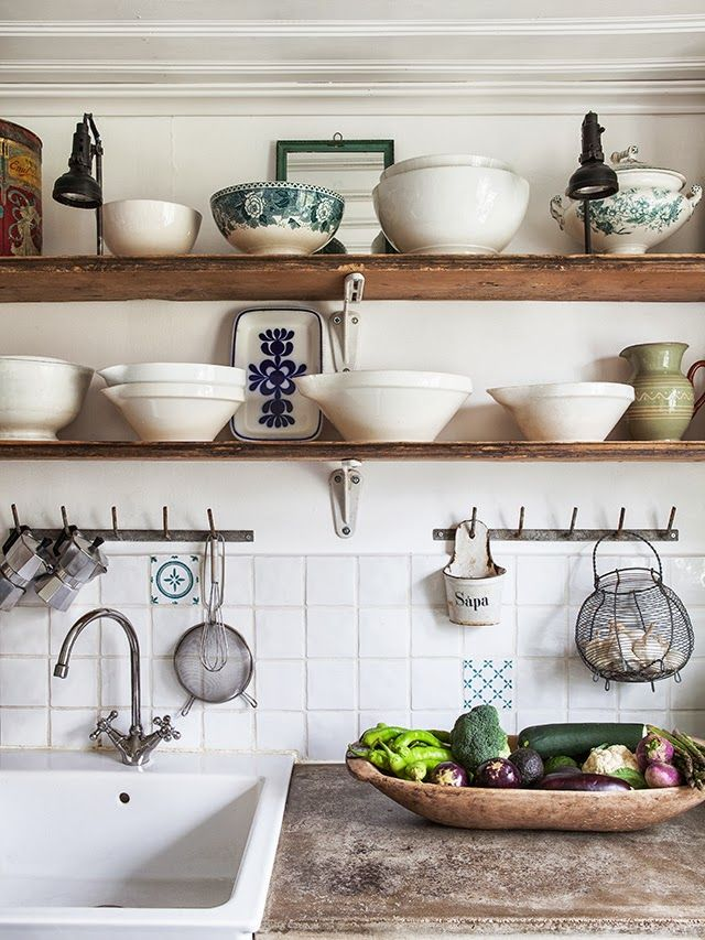 White porcelain kitchen sink rough concrete counter with wooden shelving.