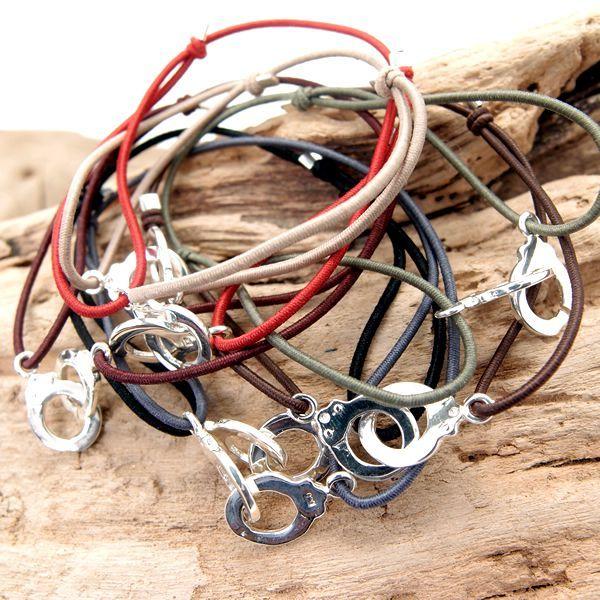 Bracelet Menottes en argent sur cordon élastiqué. Finition noeuds coulissants.