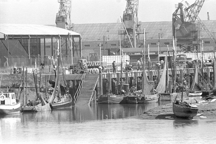 Dockside cranes overlook small fishing boats unloading shellfish at King's Lynn docks on April 10, 1968.