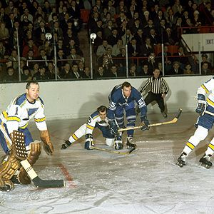 LANKY WAYNE CARLETON (25) LEANS ON DEFENSEMAN BOB PLAGER OF THE ST. LOUIS BLUES DURING GAME OF FEB. 21, 1968 AT MAPLE LEAF GARDENS. ST. LOUIS GOALIE IS HALL OF FAMER GLENN HALL, WHO STARRED EARLIER IN THE DECADE WITH THE CHICAGO BLACKHAWKS.