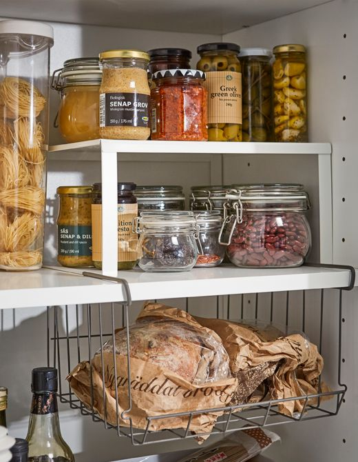 IKEA VARIERA white coated steel shelf insert and OBSERVATÖR metal clip-on basket are no-drill solutions that create more pantry shelving space for jams, jars, and bottles of different sizes.