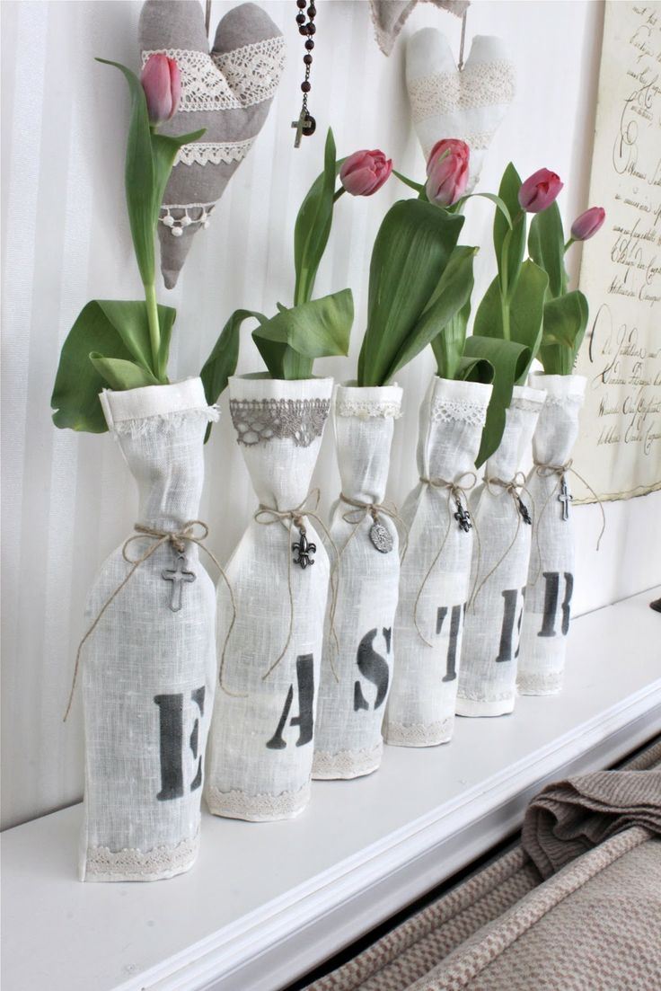 Easter mantel decor Simple Stenciled linen bags over glass bottles to dress up tulip vases