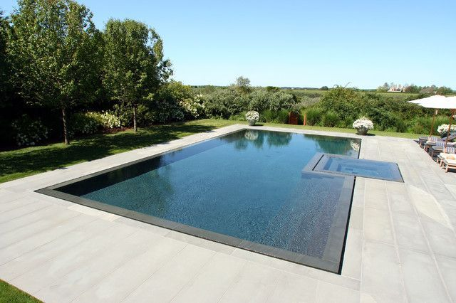 Pool trends | Knife-Edge Pools: For a slightly more upscale design give a mirrored appearance to your pool by having the water level match the pool deck level. The water flows into a slot-edge around the pool to keep it from overflowing. These pools may require a slightly more complex set-up, but it is a beautiful design that will impress everybody. #knifeedgepools #pooltrends #vanishingedgepool…