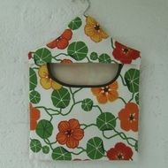 A fully lined peg bag carefully made using a bright, sturdy cotton fabric from Ikea. It's lined with a cream cotton fabric and the lower edge of the opening is bound with dark green bias binding. On a wooden coat hanger so it can hang on your line, in ...