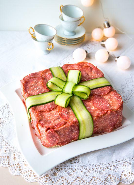 Lahjapaketti on ajankohtainen teema aina, kun juhlista on kysymys. Voileipäkakulle saa paketin hahmon helpolla ja nopealla tavalla. Sipaisu tuorejuustoa kakun pintaan riittää, minkä jälkeen ohuet meetvurstiviipaleet tarttuvat siihen vaivattomasti. Lahjanauhojen virkaa toimittaa kurkku. Meetvursti-voileipäkakku Leipäkerrokset: n. 27 viipaletta täysjyväpaahtoleipää Kostutus: 2 ½ dl maitoa Täyte: 2 maustekurkkua 2 punaista paprikaa 300 g meetvurstiviipaleita 800 g […]