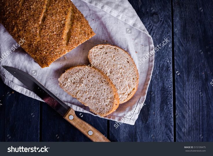 Fresh wholegrain bread and knife on rustic napkin wooden table. Horizontal image, copy space