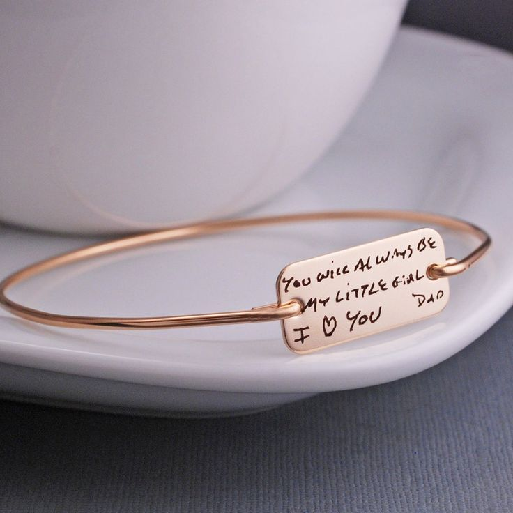 A 14k gold filled bracelet is engraved with custom handwriting. The rectangle disc measures approximately 1 inch wide by 1/2...