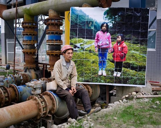 Hou Keming, a low-income laborer in Chengdu, China, sits beside an image of his daughters in rural Sichuan Province on December 6, 2011.