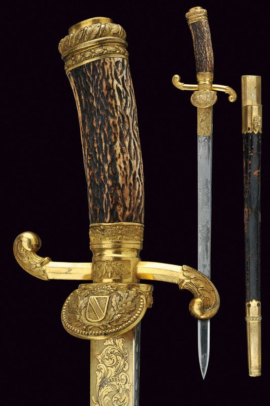 A royal Baden hunting hunger   category:   A Gentleman collect. of Oriental Arms provenance:   Baden dating:   last quarter of the 19th Century   description:   Straight, single -and false-edged blade, finely engraved with trophies and floral motifs, gilt at the base; gilt bronze hilt, at the shell-guard the crowned coat of arms of Bauden among oak branches, quillon, quillon-block and cap decorated en suite; deer horn grip.