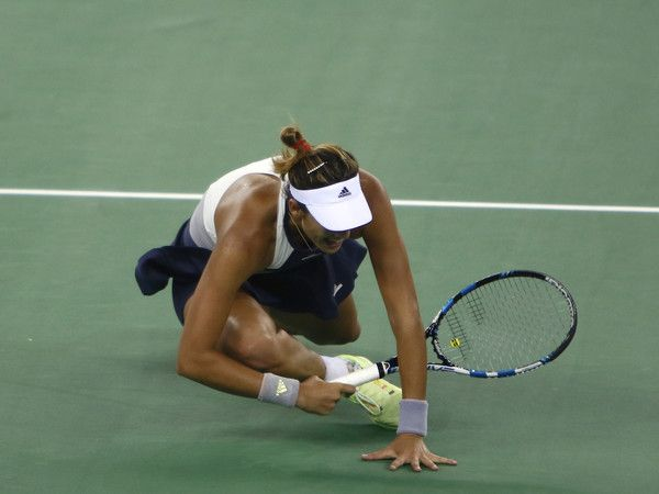 Angelique Kerber Garbine Muguruza Photos Photos - Garbine Muguruza of Spain falls on the ground during the match against Angelique Kerber of Germany on day 6 of 2015 Dongfeng Motor Wuhan Open at Optics Valley International Tennis Center on October 2, 2015 in Wuhan, China. - 2015 Wuhan Open - Day 6