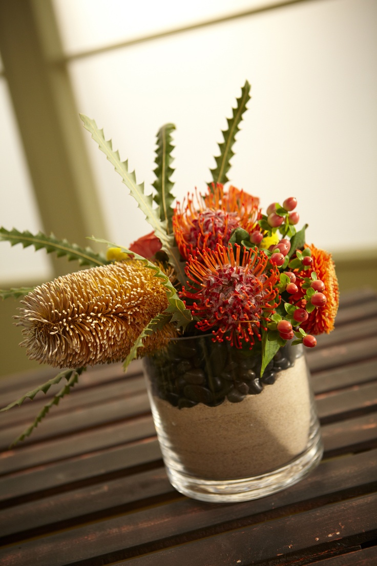 Sand and Stone are Landscaped between two cylinder vases... with textures of Banksia and Pincushion Protea... Gerandos, Orange Spray roses, Hypericum and Crespedia (*Globe Yarrow)....  - More Great Ideas from DriedDecor.com