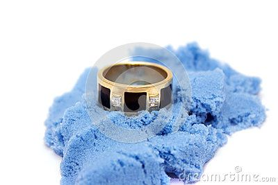 Ring with diamonds lays on blue sand
