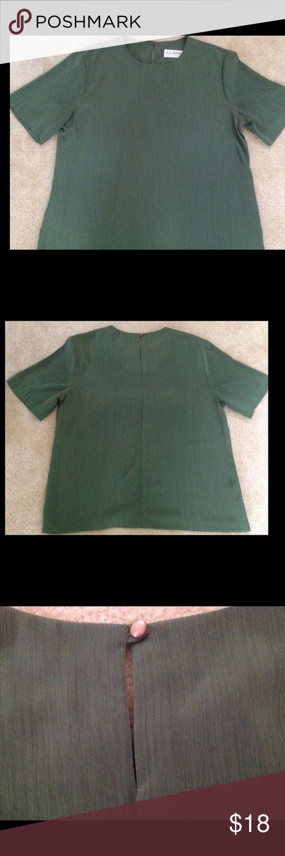 """Vintage Susan Graver Olive Green Size Medium Shell Susan Graver designs timeless clothing pieces. This vintage short-sleeved shell is no exception. It is easy to pull on because there is a button closure in the back.  The fabric is a slinky microfiber that makes the green almost appear to be striated.  It is well-made with a neck facing that gives the neckline body and substance.  The sleeves are the perfect length - allowing for good coverage.  The top measures 25."""" Machine wash and tumble…"""