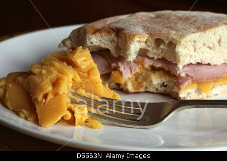 A pease pudding and ham sandwich is served in stottie cake and a side serving of pease pudding. Stock Photo