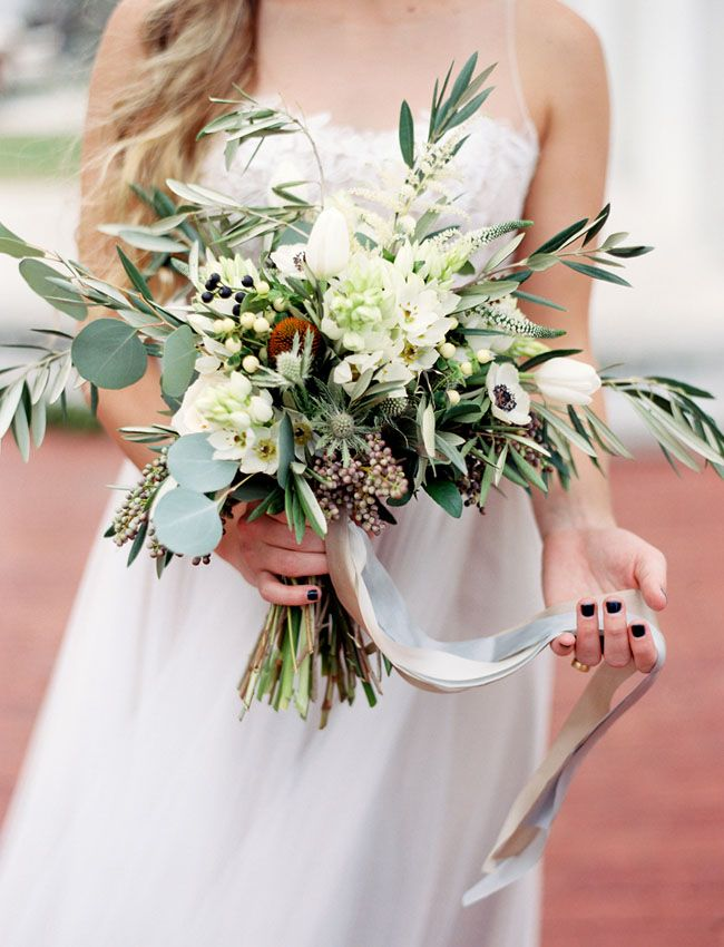 "Foliage inspired bouquet - The floral elements used were olive branches, various species of eucalyptus (""silver dollar"" and ""seeded""), white anemone, deep blue anemone, white ornithogalum (aka ""star of bethlehem""), peach hypericum berries, Quicksand roses, privet berries, ligustrum berries, white eryngium (""silver ghost"" thistle), blue eryngium (""sea holly"" thistle), white astilbe, white veronica, and white tulips."