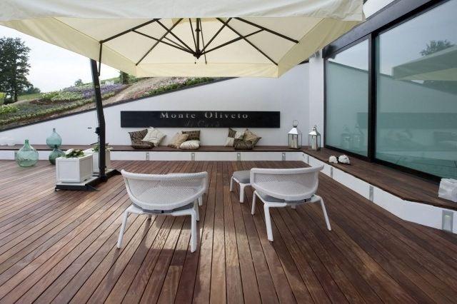 lames de terrasse en ipé de couleur marron et deux chaises longues blanches