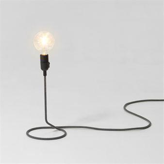 Cord från Design House Stockholm har en enkel och avskalad men samtidigt effektfull design. Från en ringlande sladd reser sig lampan och sprider ett varmt sken. Designad av den svenska trion Form Us With Love.