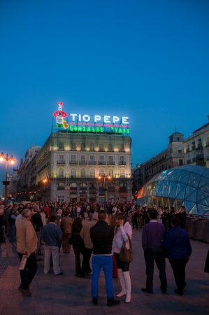 #Madrid plaza crowd at nightfall underneath glowing Tio Pepe sign