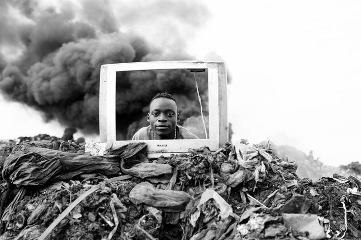 A young boy is playing behind a discarded TV frame at the Hulene dump in Maputo…