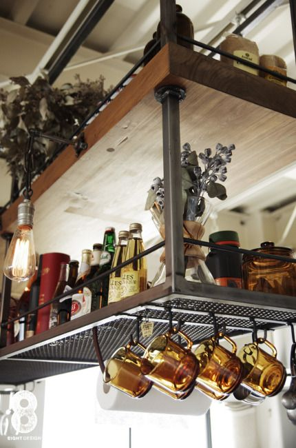 キッチンの吊り棚はスチールと寿司屋のカウンターをリメイクして制作。 キッチンペーパーをレザーベルトでぶら下げる収納アイデアが楽しい。