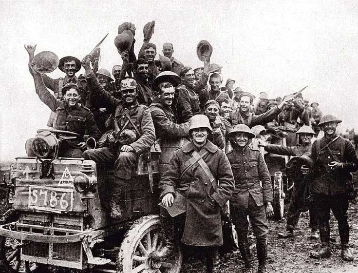 First World War: Canadian troops in festive mood as they begin a rotation away from the trenches. Note two of the troopers in the foreground wearing German helmets -- a Pickelhaube and the classic steel helmet, 1916.