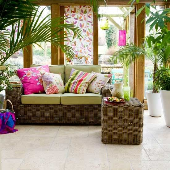 This classic-style conservatory has been given a modern twist with bold prints in orchid shades. Rattan furniture keeps the look relaxed and comfortable, while a colourful leaf blind adds interest to the windows.