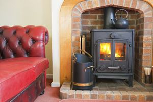 Wood-burning stove in fireplace, nice shape of the brickwork around the fireplace