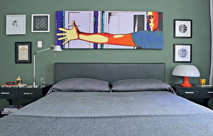 Em seu quarto, o arquiteto Mario Celso Bernardes escolheu uma tinta de cor verde exército para a parede atrás da cabeceira. A cama é estofada de couro em tom chumbo. Seu rosto ilustra a tela de Flavio Mayumi. À esquerda, diploma do caminho de Santiago de