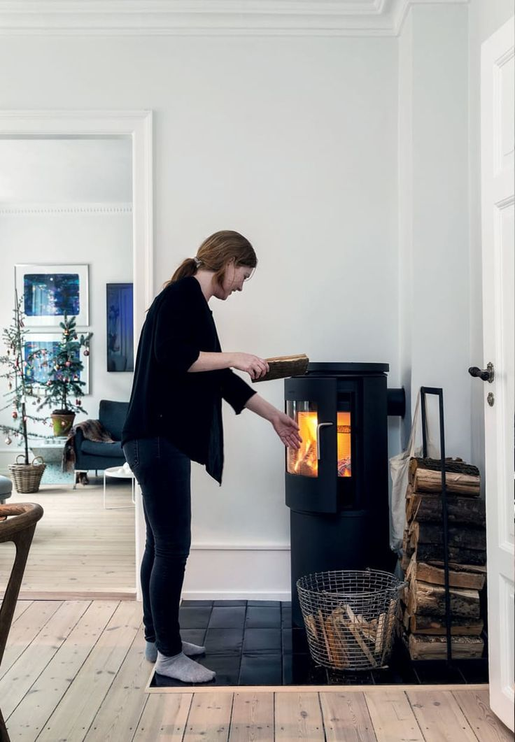 Simple and freestanding fireplace in the dining room with smart storage solutions for the firewood.