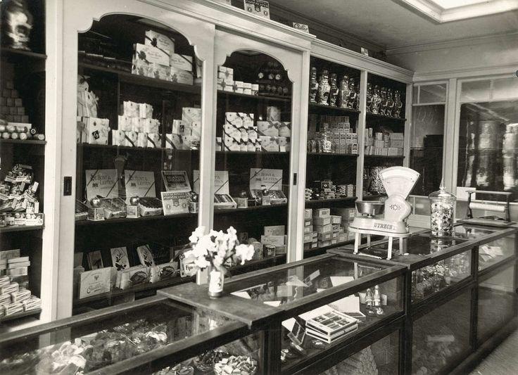 Interieur van winkel in koloniale waren, comestibles en chocolade van J. van der Tas aan het Leidseplein te Amsterdam. Achter de toonbank een veelheid aan koopwaar in vitrinekasten. Nederland, 1917.