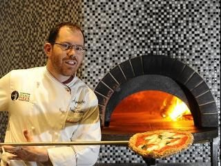 Pizza maker Francesco Spataro making a Margherita Bufala in his woodfire oven, burning up - Aperativo Leichhardt