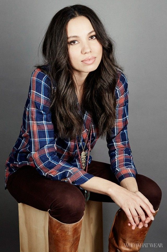 Jurnee Smollett-Bell wears a plaid shirt, layered pendant necklace, burgundy jeans, and knee-high boots