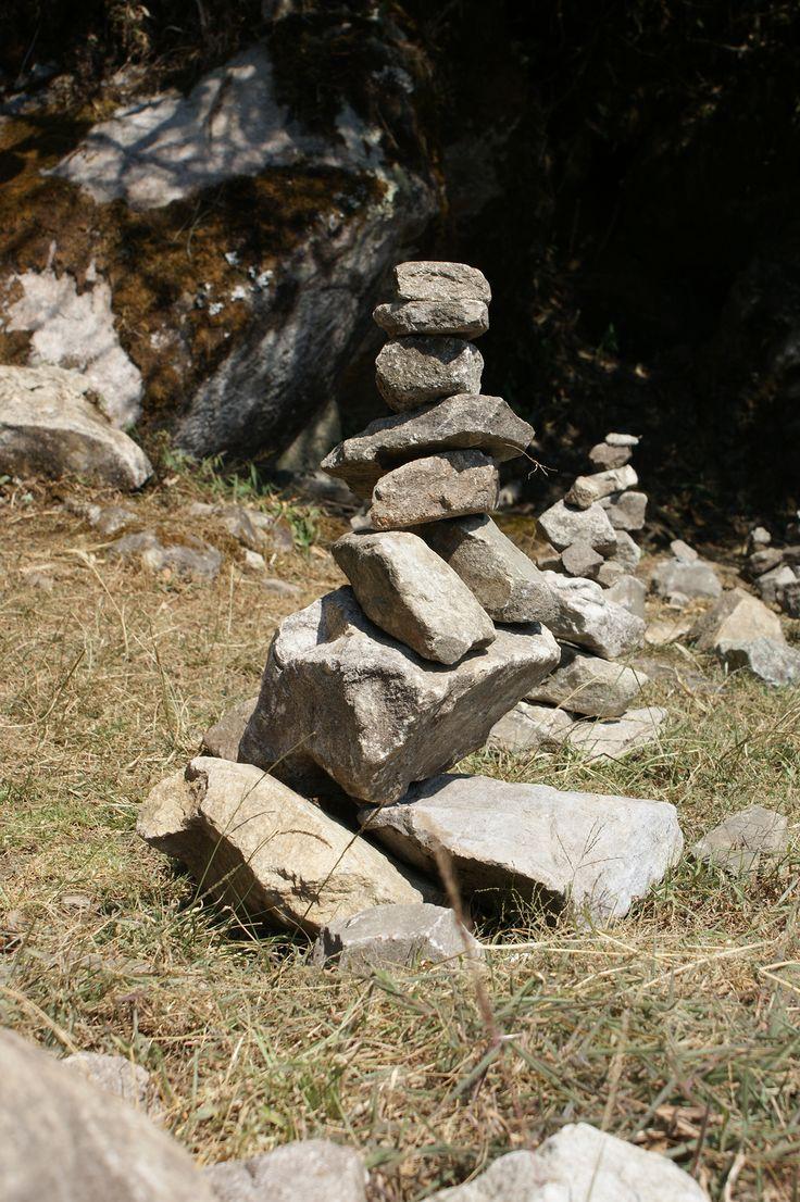 INSPIRACIÓN [Contexto local] La palabra APACHETA, proveniente de nuestro quechua, se refiere a un montículo de piedras sobrepuestas, colocadas una sobre otra, en forma cónica ascendente. Esta costumbre ancestral cumple la función de ser una ofrenda, ya sea a la Pachamama, a los Apus o a otras divinidades que forman parte de la cosmovisión andina. Son los viajeros los que las ofrecen, buscando estar en armonía con el entorno o como buen augurio para el camino aún por recorrer.