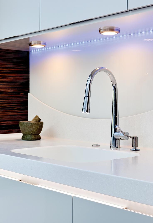 Beautiful blue LED lighting brightens up this slick white kitchen.