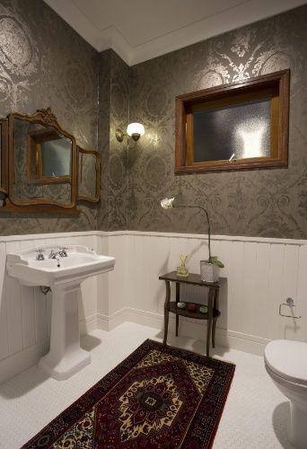 A janela máximo ar (Cedro Arana) é um elemento contemporâneo incorporado ao lavabo social, com papel de parede adamascado, barrado com moldura de madeira e louça em coluna e estilo clássico.