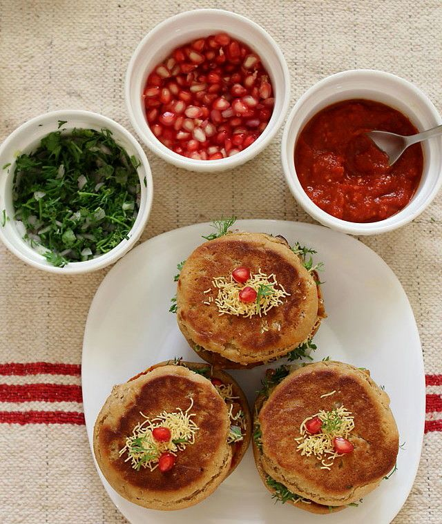 Dabeli - Indian Burger street food. A spicy, tangy sweet potatoe fillinf drizzled in spicy chutney, onions, sev, and even pomegranate