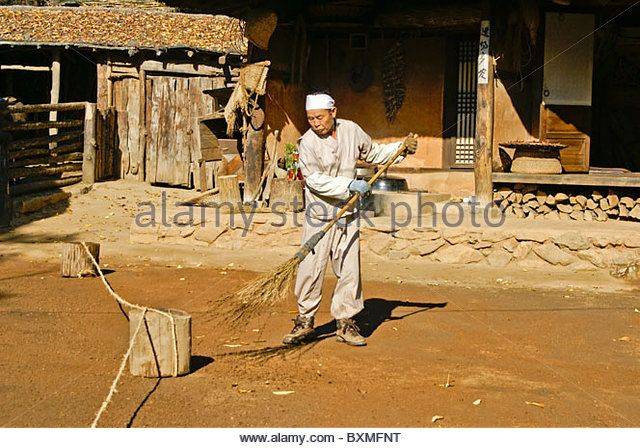 Man sweeping yard, Korean Folk Village, South Korea - Stock Image
