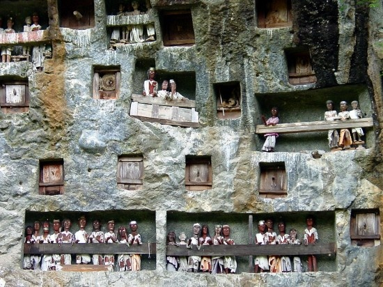 "This is Lemo, a burial sites with holes carved to fit coffins and balconies for the ""tau tau"" – life-size wooden effigies representing the deceased. Tana Toraja (a tribe that still honors the old Austronesian lifestyle, similar to Nias culture), South Sulawesi, Indonesia."