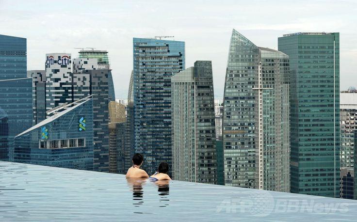 シンガポールの高級リゾートホテルのマリーナ・ベイ・サンズ(Marina Bay Sands)の屋上にある「インフィニティープール(Infinity Pool)」でくつろぐ人々(2014年5月20日撮影)。(c)AFP/ROSLAN RAHMAN ▼23May2014AFP 高級ホテルの屋上プールで景色を満喫、シンガポール http://www.afpbb.com/articles/-/3015704 #Marina_Bay_Sands #Infinity_Pool