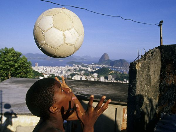 In the Santa Teresa favela, a child plays with a soccer ball, while Pão de Açúcar (Sugarloaf) stands tall in the background.