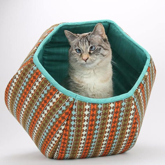 This cat bed is made in a striped Southwestern fabric. Our Cat Ball® cat bed is a modern pet bed with two openings. This is a turquoise and brown cat bed. The shell fabric is a Southwestern influenced stripe, and the lining is a coordinating turquoise. This Cat Ball® cat bed coordinates with another Cat Ball® made with fabrics from the same collection. The Cat Ball® is our original modern pet bed design. Our six panel pet bed offers a covered, private napping spot with with two...