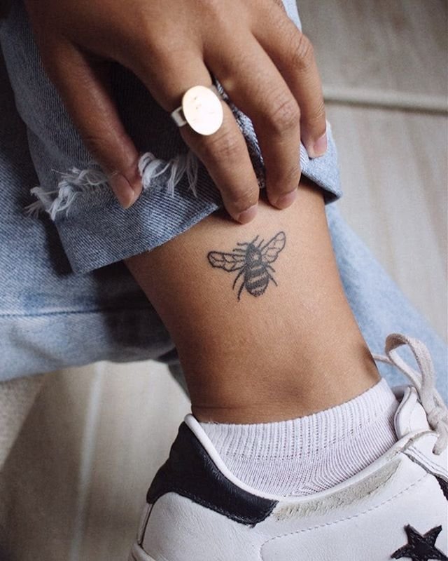 A small black bee tattoo on the left ankle