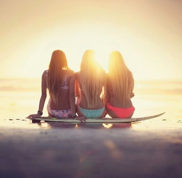 Sitting on a surf board watching the sunset. AWwW summer days!!! This looks like me and my sisters!