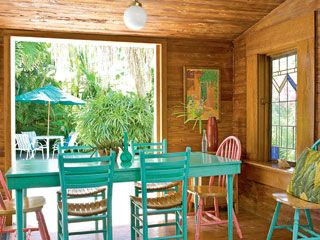 Key West Dining Room - Painted aqua and pink, the dining table and chairs make a playful statement in this Key West, Florida space. Pine wood paneling from Dade County, Georgia balances out the strong color palette
