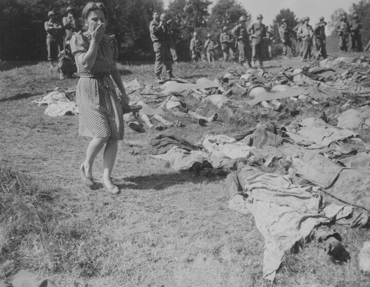 A German girl is overcome as she walks past the exhumed bodies of some of the 800 slave workers murdered by SS guards near Namering, Germany, and laid here so that townspeople may view the work of their Nazi leaders, May 17, 1945.