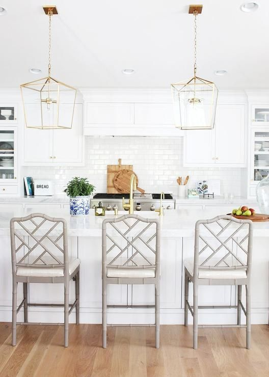 Three gorgeous gray bamboo counter stools sit on light oak wood floors in front of a white kitchen island finished with a carrera marble straight edge countertop holding a sink with a brass gooseneck faucet beneath Regina Andrew Design Camden Five-Light Lanterns.