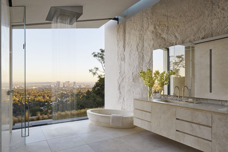 Open concept bathroom with a prominent rainfall shower offers a stunning view of Los Angeles. [2000 x 1333]