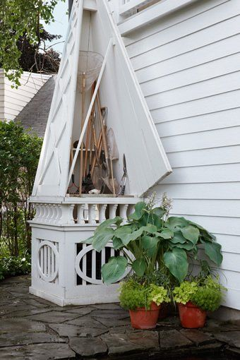 Hidden garden tool and air condition unit storage using a large decorative obelisk designed by Art Harrison Interiors.