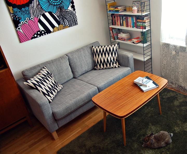 Grå soffa och mönstrade kuddar. Retrobord. Stringhylla.