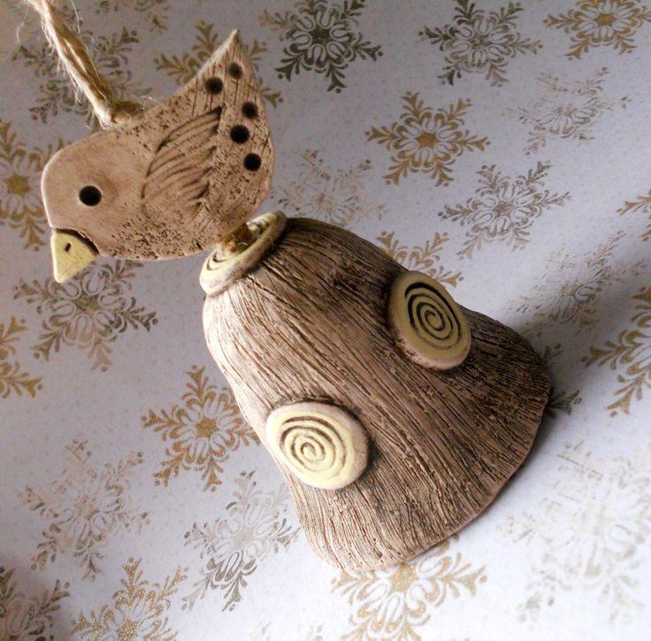 Zvoneček s ptáčkem Keramický zvonek, ručně modelovaný, patinovaný burelem. Detaily malované žlutou engobou. Výška zvonku je 7 cm.
